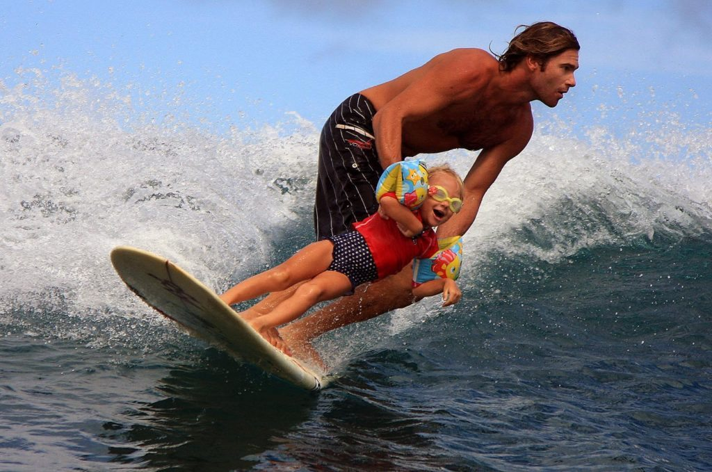 Father and daughter surf